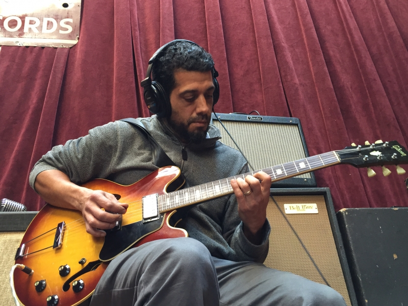 A photo of Babak Tondre playing guitar in the Wide Hive Studio.
