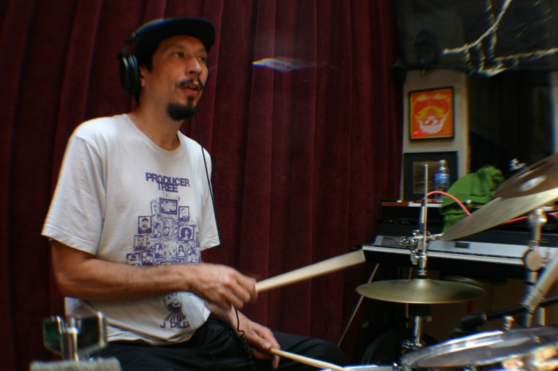 A photo of Josh Jones sitting at his drum set, playing the drums in the Wide Hive Studio.