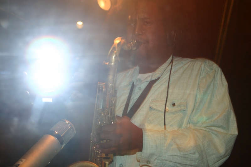 Kamasi Washington in a white long sleeved shirt, playing the saxophone on a live stage, with a bright light shining behind him.