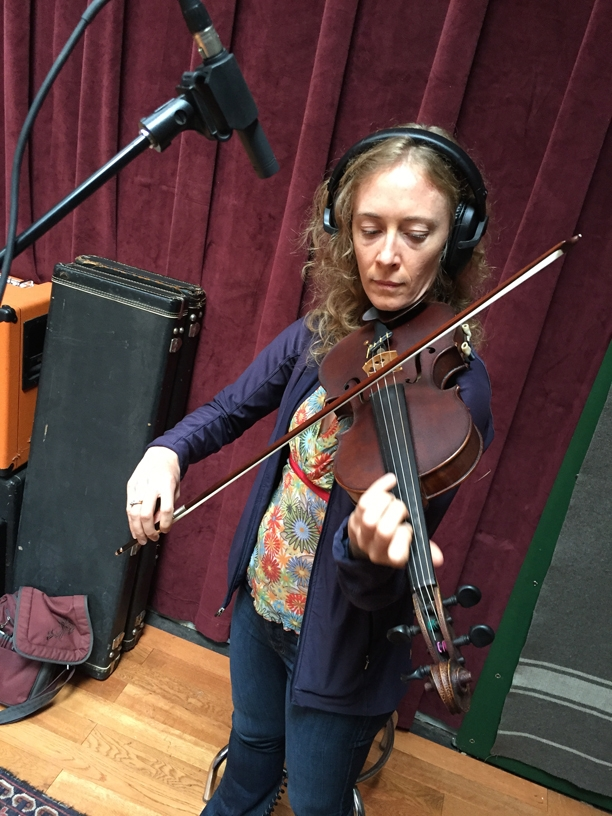 A photo of Laurel Thomsen with her violin, at the Wide Hive Studio.