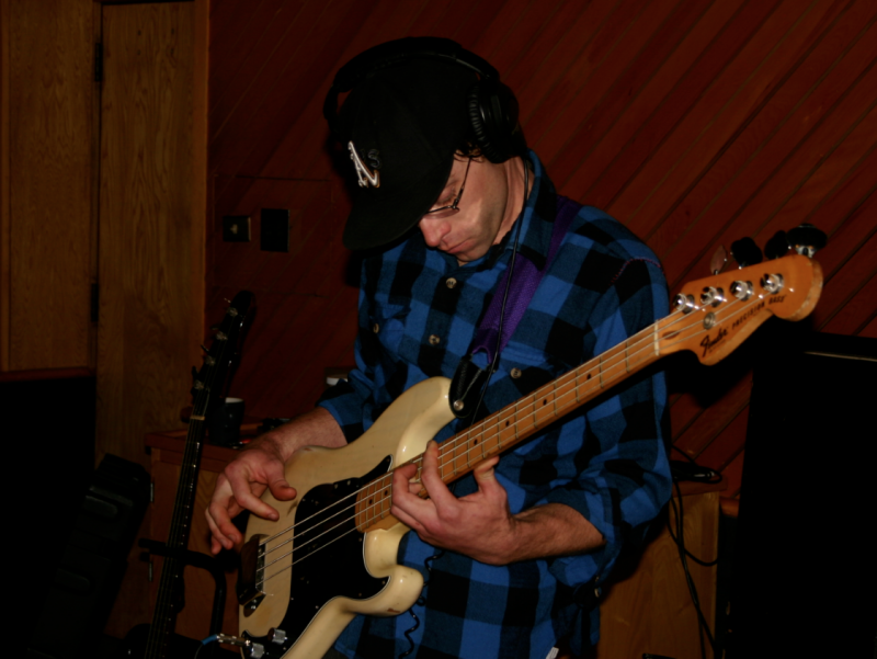 A photograph of Matt Montgomery playing bass in the Wide Hive Studio.