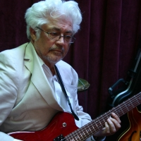 Larry Coryell in a white coat with his eyes closed, playing the guitar.