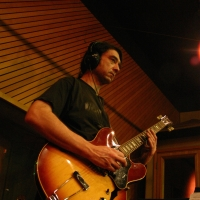 A photo of Mike Ramos playing guitar in the Wide Hive Studios.